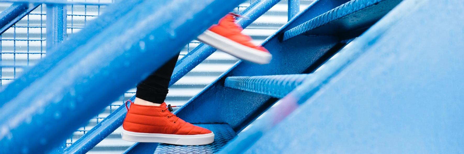 Berufliche Rolle, Führungsverhalten, neue Aufgaben oder Kommunikationscoaching: Bringen Sie jetzt mit Business Coaching Dinge in Bewegung! Das Bild zeigt rote Turnschuhe, die auf einer Treppe nach oben gehen.